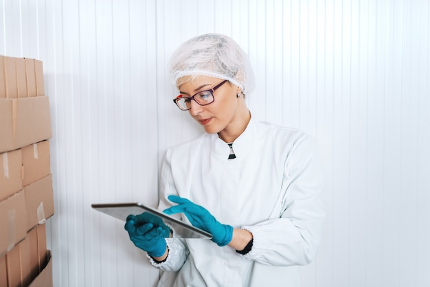 Empregada loira em uniforme estéril usando tablet para logística em pé ao lado de caixas na fábrica de alimentos.