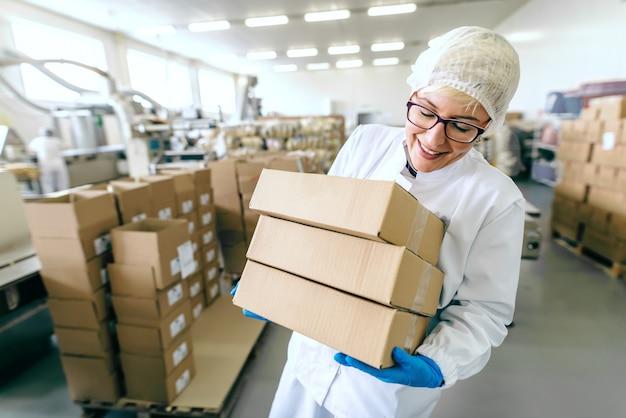 Empregada loira sorridente em uniforme estéril e com óculos colocando caixas na pilha. interior da fábrica de alimentos.