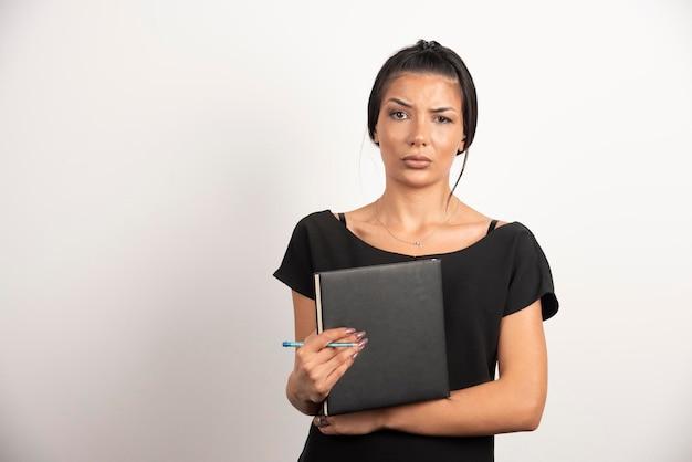 Empregada morena com notebook posando na parede branca.
