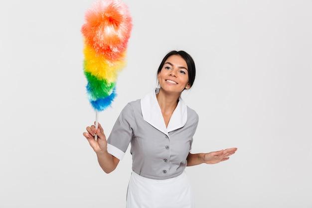Empregada morena feliz em furto uniforme cinza com espanador