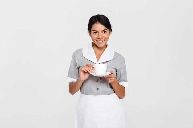 Empregada muito sorridente em uniforme cinza descansando e bebendo chá em pé