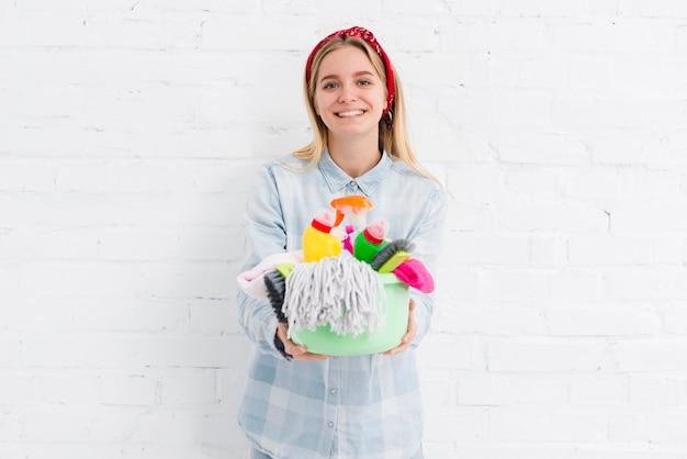 Empregada sorridente com produtos de limpeza