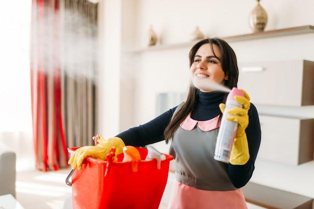Empregada sorridente em uniforme e luvas de borracha borrifa ambientador no quarto de hotel. equipamento profissional de limpeza, faxineira