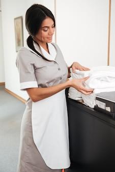 Empregada sorridente tomando toalhas limpas de um carrinho de limpeza