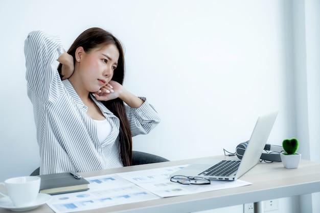 Empregada triste empresária asiática infeliz trabalhando com entediado no laptop e gráfico no escritório