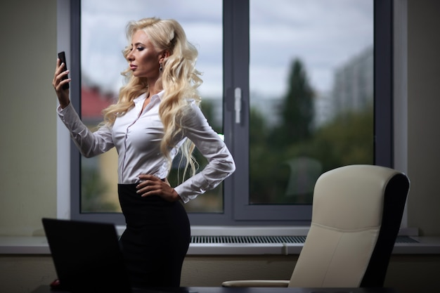 Empregado atraente no escritório usa um smartphone perto da janela