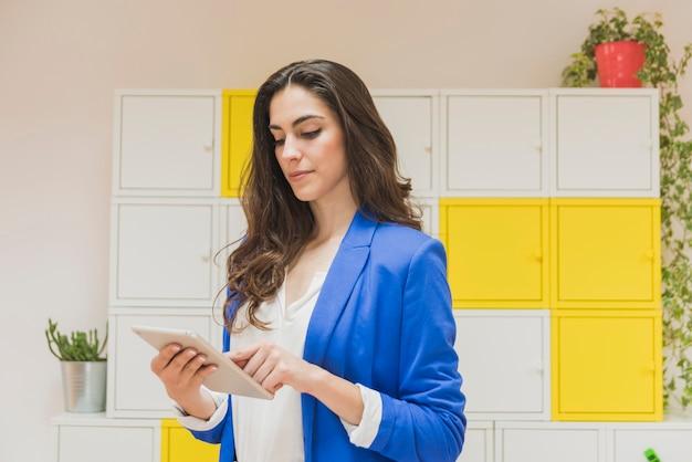Empregado bonita verificar seu tablet no escritório
