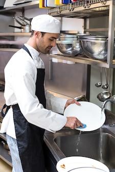Empregado considerável que lava pratos