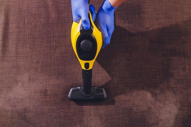 Empregado da tinturaria que remove a sujeira da mobília no apartamento, close up.