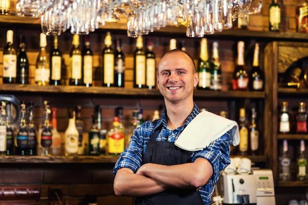 Empregado de bar no trabalho no bar, retrato de trabalhador de barman alegre em pé, garçom dando menus, um pub. bar.restaurant.classic.evening.european restaurant.european bar.european restaurant.american bar.american bar.