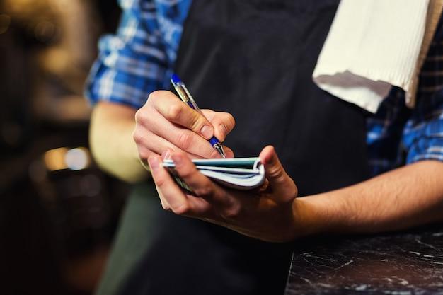 Empregado de bar no trabalho no pub, o garçom recebe um pedido, garçom dando menus, um pub.