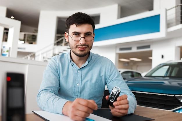 Empregado de concessionária segurando uma chave de carro