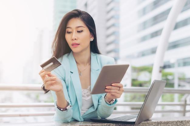 Empregado de empresa jovem negócios segurando computador tablet telefone e cartão de crédito usa um cartão de crédito pagar compras online com conveniência e facilidade - conceito de compras online feminino de estilo de vida