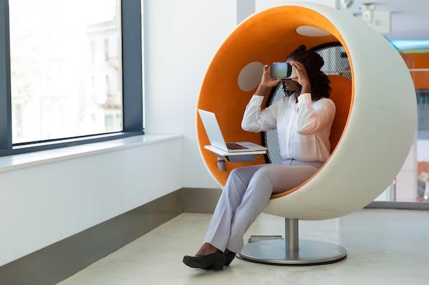 Empregado de escritório feminino com laptop assistindo apresentação virtual