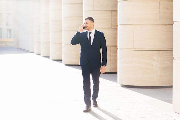 Empregado de escritório masculino liga para alguém via celular moderno, usa roupa formal