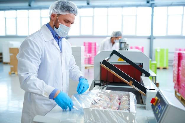 Empregado de fábrica de confeitaria, caixa de embalagem em filme de embalagem