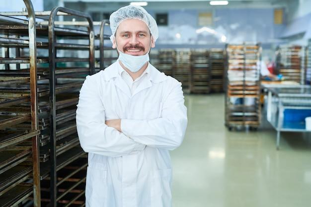Empregado de fábrica de confeitaria em pé e sorrindo