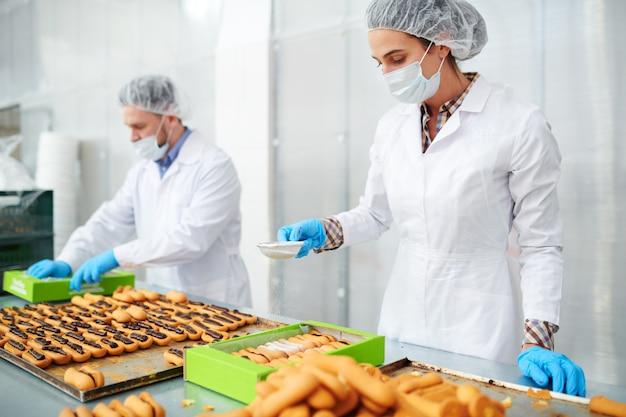 Empregado de fábrica de confeitaria espanando massa com açúcar de confeiteiro
