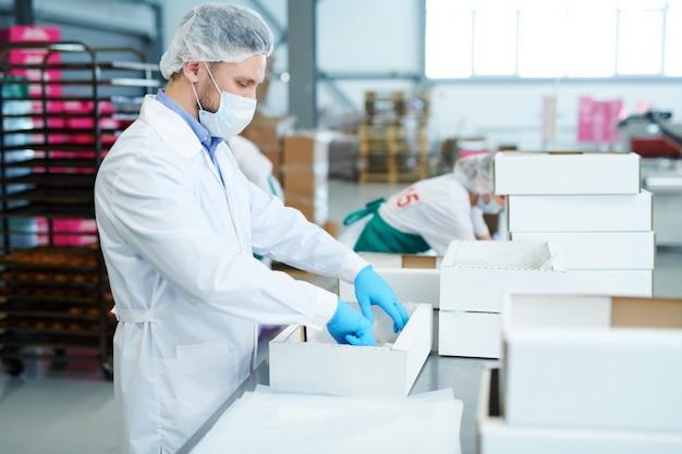 Empregado de fábrica de confeitaria, preparando a caixa vazia