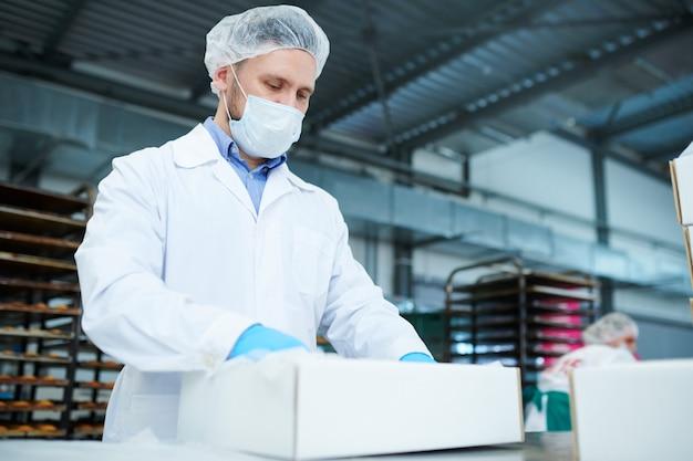 Empregado de fábrica de confeitaria, preparando o pacote