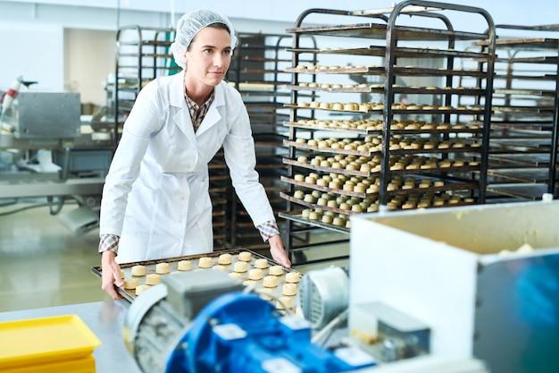 Empregado de fábrica de confeitaria, segurando a bandeja com massa não cozida