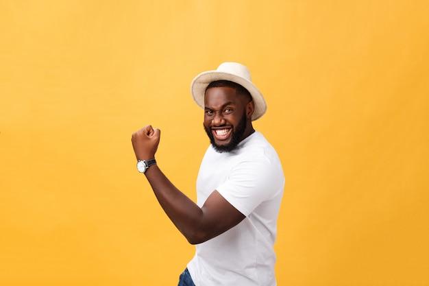 Empregado de homem afro-americano jovem bonito sentindo animado, gesticulando ativamente, mantendo os punhos cerrados