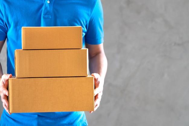 Empregado de homem de correio de serviço de entrega em uniforme de camiseta azul segurando caixas de papelão vazias ou encomendas na mão.