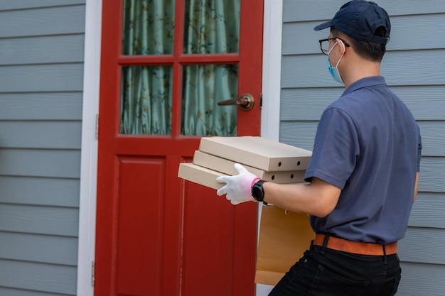 Empregado de homem entrega na máscara uniforme de boné de boné azul e luvas médicas oferece comida para viagem. serviço de entrega em quarentena, surto de doença, condições pandêmicas de coronavírus covid-19.