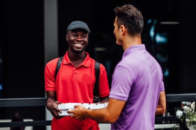 Empregado de homem sorridente pegando a caixa de pizza do jovem afro-americano de correio, ordenou o serviço de entrega de comida de refeição na pausa para o almoço corporativo.
