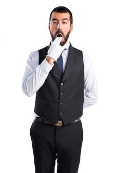 Empregado de luxo que faz o gesto de vômito
