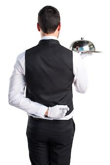 Empregado de luxo que segura uma bandeja