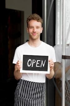 Empregado de mesa com avental segurando sinal aberto