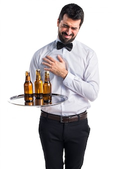 Empregado de mesa com garrafas de cerveja na bandeja com dor no coração