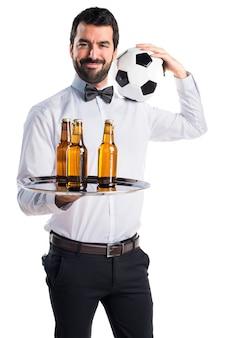 Empregado de mesa com garrafas de cerveja na bandeja segurando uma bola de futebol