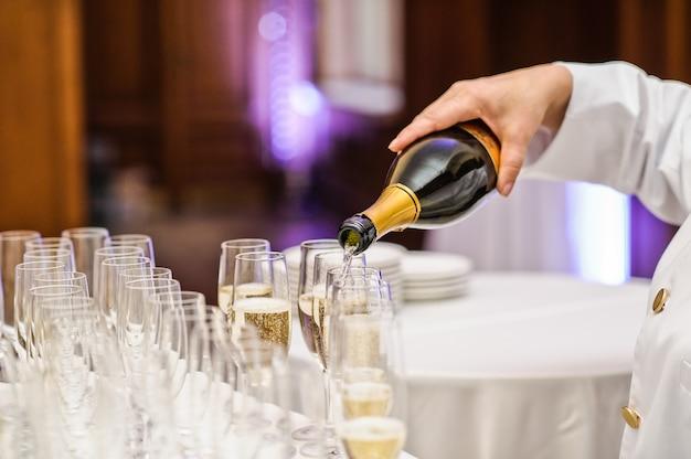 Empregado de mesa que derrama o champanhe no vidro de vinho no restaurante.