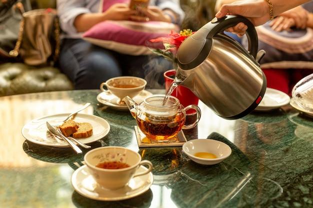 Empregado de mesa que enche a água quente no bule do chá para o cliente com pice do bolo na tabela.
