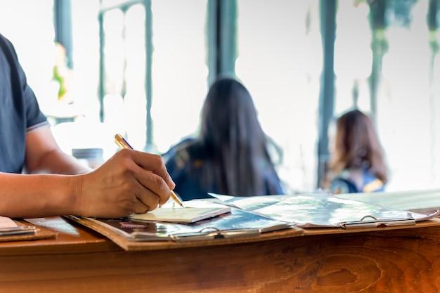 Empregado de mesa que escreve abaixo a ordem do cliente na barra do contador no café.