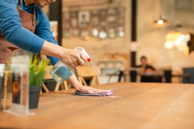Empregado de mesa que limpa a tabela com o desinfetante do pulverizador na tabela no restaurante.
