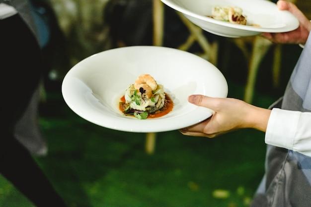 Empregado de mesa que serve petiscos durante um casamento.
