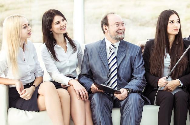 Empregado de mulher jovem e bonita faz uma selfie com seu chefe e equipe de negócios, sentado perto da janela no escritório.