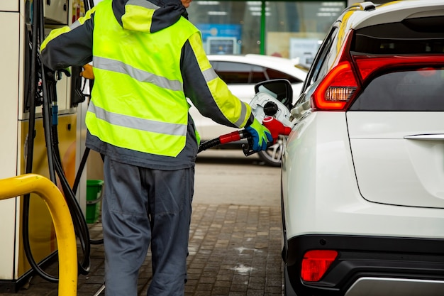 Empregado de posto de gasolina de macacão reabastecendo o carro com gasolina close-up. sem rosto