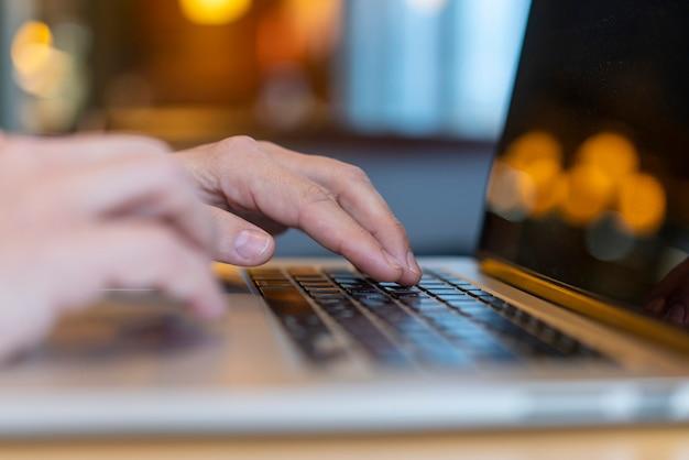 Empregado, digitando no laptop com bokeh