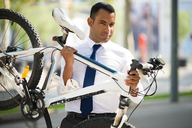 Empregado do escritório bonito que carrega sua bicicleta quebrada