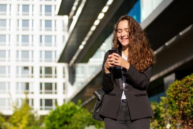 Empregado do sexo feminino alegre aprender boas notícias de mensagem de texto