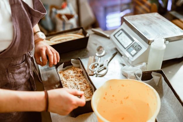 Empregado espalha a massa crua em um prato com um garfo na mesa de metal