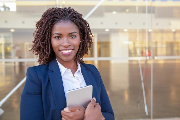 Empregado feliz com tablet posando perto de prédio de escritórios