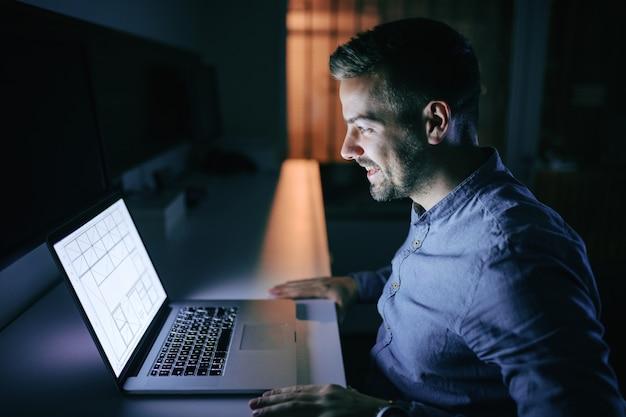 Empregado feliz trabalhando no projeto e sentado no escritório tarde da noite.