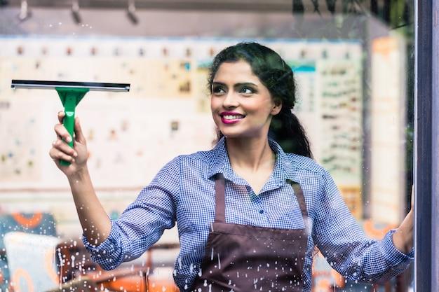 Empregado indiano limpando janelas