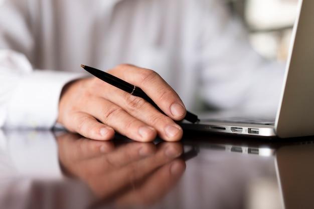 Empregado irreconhecível, segurando a caneta close-up