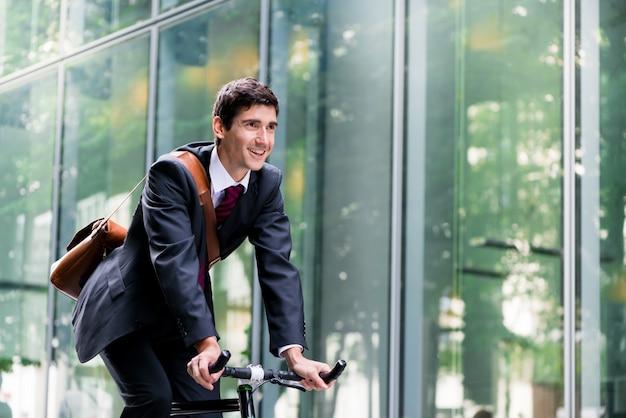 Empregado jovem alegre, montando uma bicicleta de utilitário em berlim